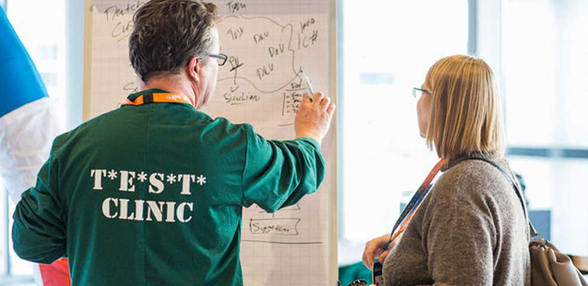 A test clinic doctor helping a EuroSTAR delegate solve a problem on a whiteboard